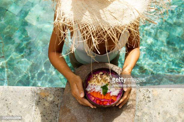 woman's hand with smoothie bowl in swimming pool. - tropical climate stock pictures, royalty-free photos & images