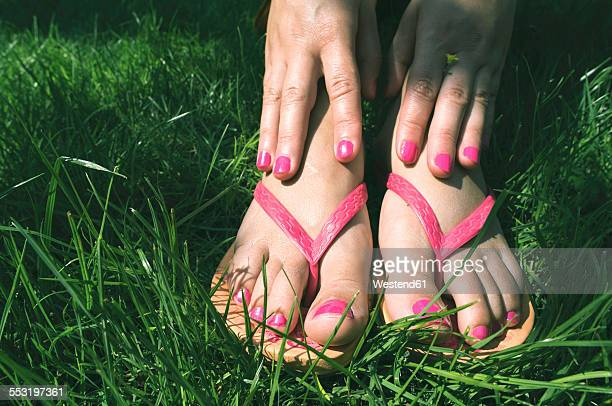 Womans hands and feet on a meadow