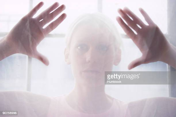 Woman's hands behind translucent glass
