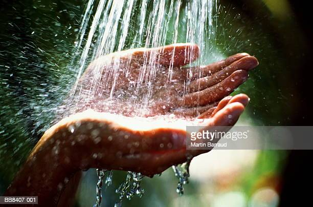 Woman's hands beneath shower of water, outdoors, close-up