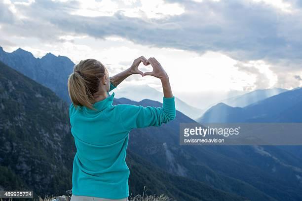 Woman's hands create heart shape, above mountain landscape