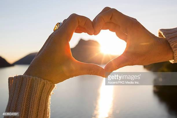 Woman's hands create heart shape at lake, sunrise