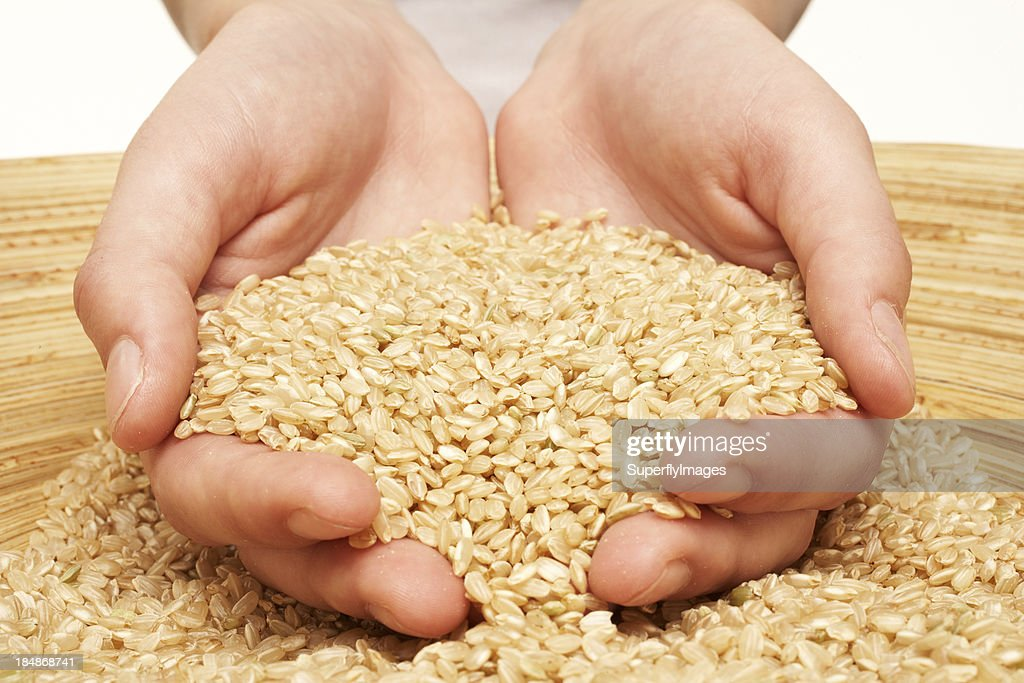 Woman's hands cup brown rice in a bamboo bowl. Close-up. : Stock Photo