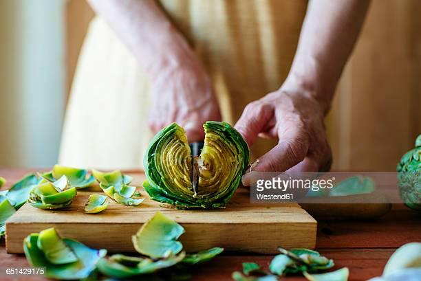 Womans hands cutting an artichoke, close-up