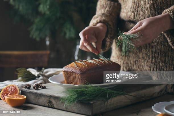 woman's hands decorating homemade christmas cake - christmas cake stock photos and pictures