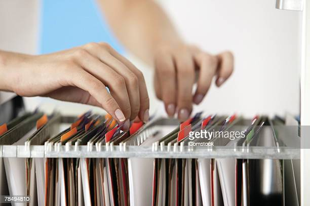 Woman's hands going through files in cabinet