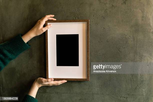 woman's hands holding and supporting picture frame on the wall. - putting stock pictures, royalty-free photos & images