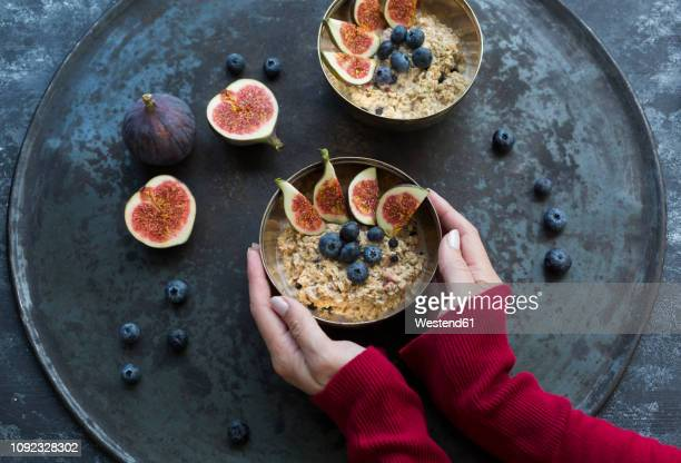 woman's hands holding bowl of porridge with sliced figs, blueberries and dried berries - oats food stock pictures, royalty-free photos & images