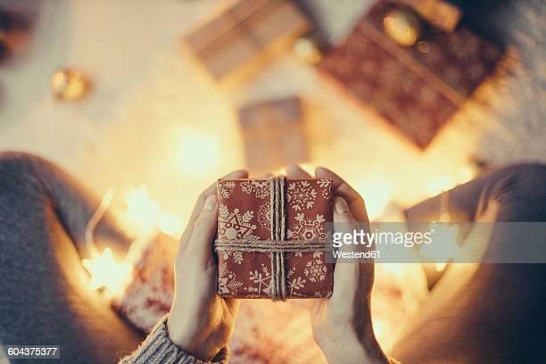 woman's hands holding christmas present - gift lounge stock-fotos und bilder