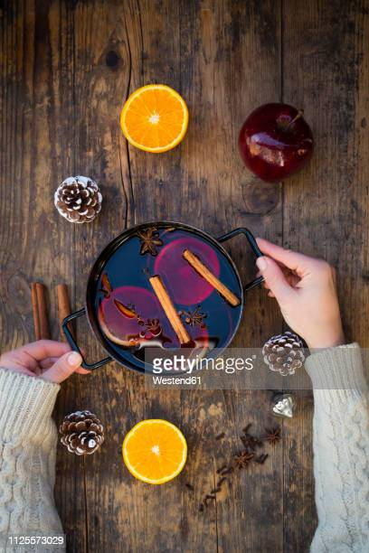 woman's hands holding cooking pot of mulled wine with orange slices and spices - gewürznelke stock-fotos und bilder