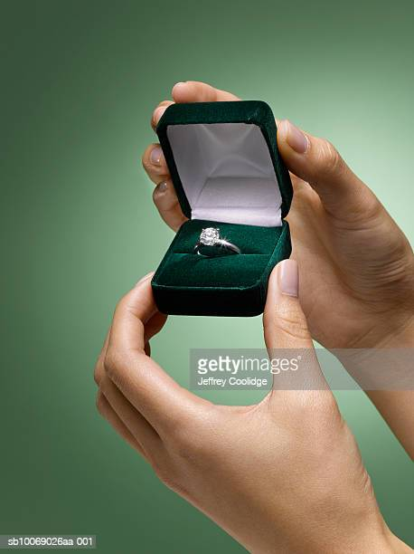 Woman's hands holding diamond ring in box, close-up