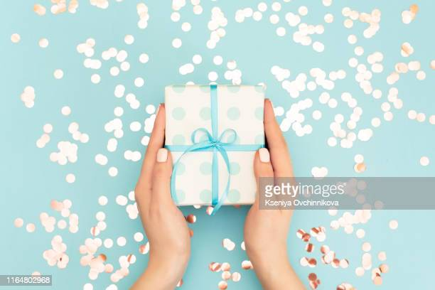 womans hands holding gift or present box decorated confetti on pink pastel table top view. flat lay composition for birthday or wedding. - happy birthday vintage stockfoto's en -beelden