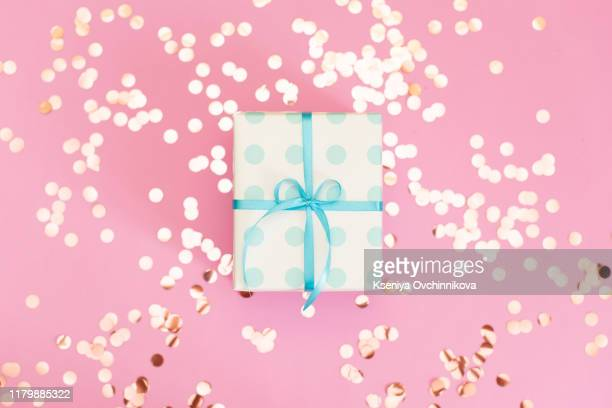 womans hands holding gift or present box decorated confetti on pink pastel table top view. flat lay composition for birthday or wedding. - wedding background stock pictures, royalty-free photos & images