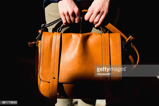 Womans hands holding leather bag, close-up