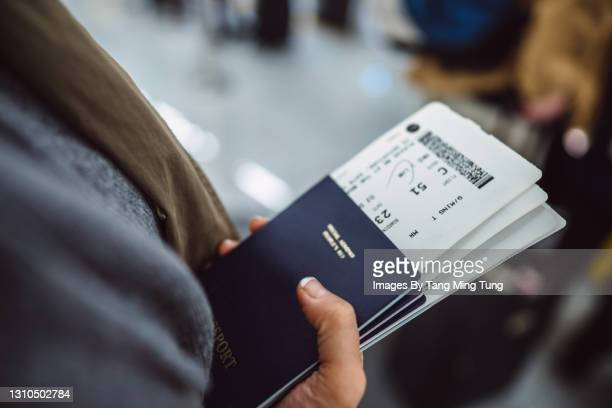 woman's hands holding passports & boarding passes of her family while waiting at the check-in counter in the airport - airport stock pictures, royalty-free photos & images