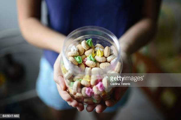 woman's hands holding plastic jar of iced gems cookies - シンガポール文化 ストックフォトと画像