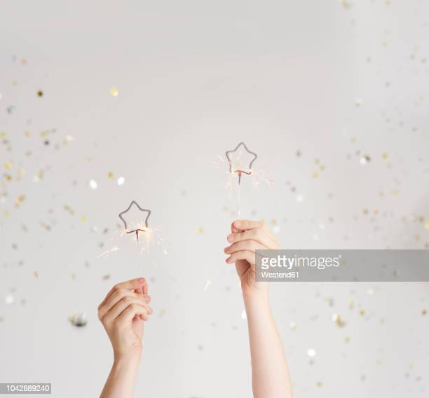 woman's hands holding sparklers - human hand stock pictures, royalty-free photos & images