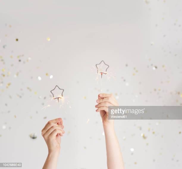 woman's hands holding sparklers - mano umana foto e immagini stock