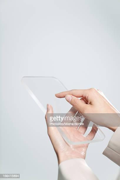 Woman's hands holding transparent digital tablet