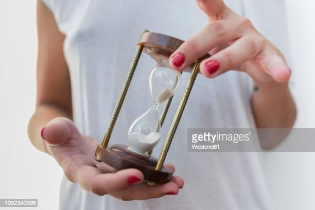 woman's hands holidng an hourglass - día fotografías e imágenes de stock