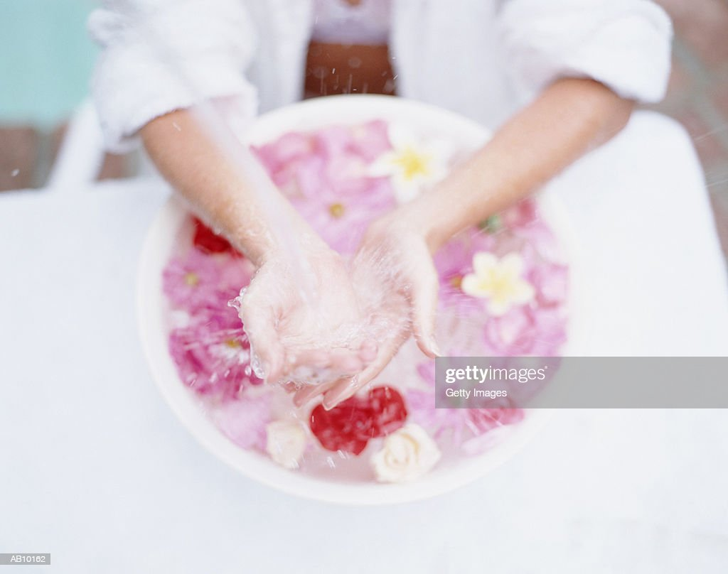 Woman's hands in bowl of floating flowers : Stock Photo