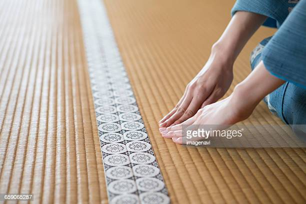 Womans hands in kimono placing on Tatami