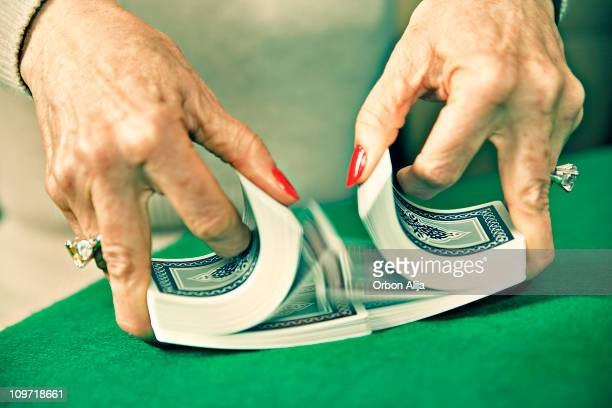 woman's hands mixing and shuffling deck of cards - shuffling stock photos and pictures