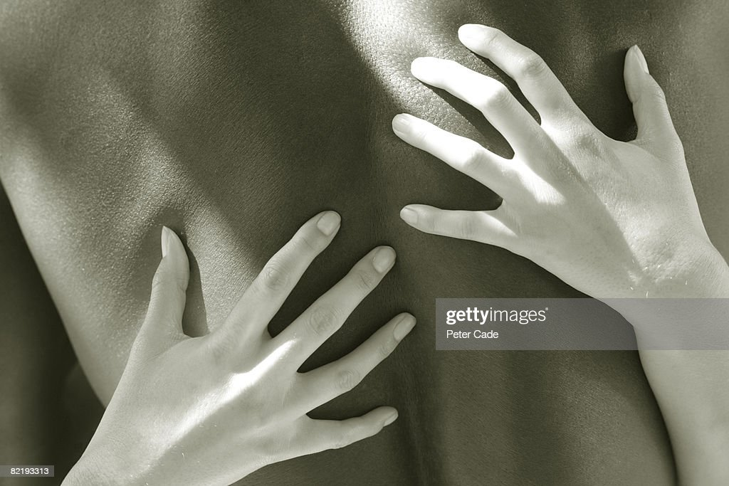 Womans hands on mans back : Stock Photo