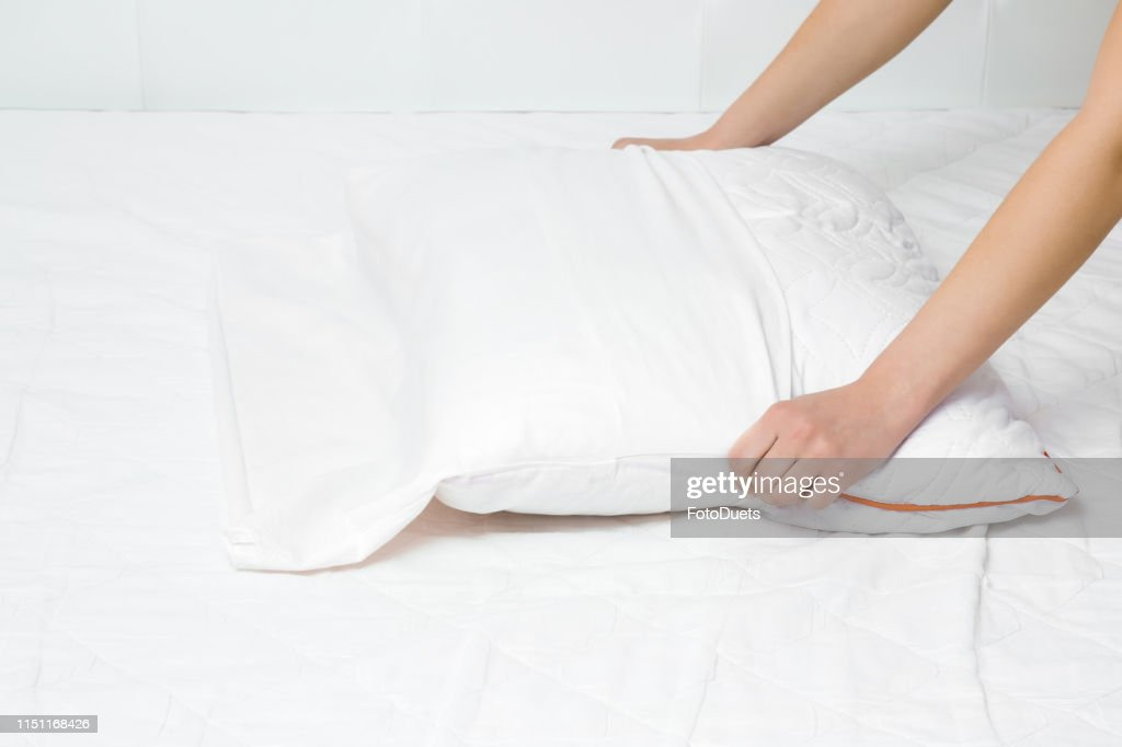 Woman's hands on mattress surface changing white cotton cover on pillow. Regular bed linen change. Closeup. : Stock Photo