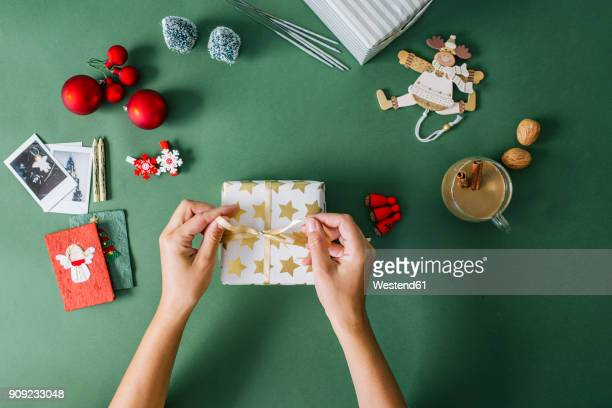 woman's hands packing christmas gift - avvolto foto e immagini stock