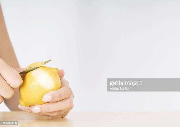 Woman's hands peeling lemon