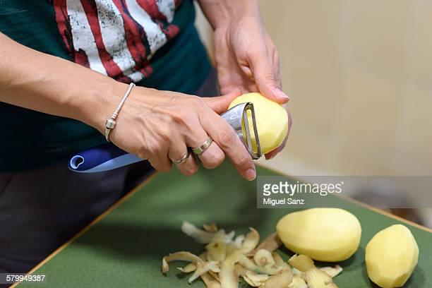 woman's hands peeling potato with a peeler - dunschiller stockfoto's en -beelden