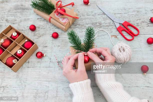 woman's hands placing decoration on christmas gift - gift lounge stock-fotos und bilder