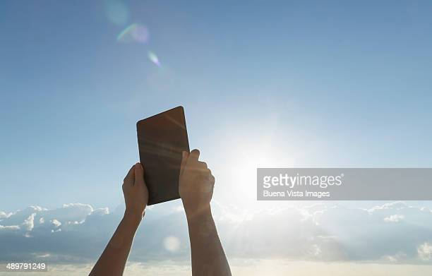 Woman's hands pointing tablet to sun