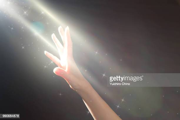 woman's hands reaching a glowing light - deus imagens e fotografias de stock