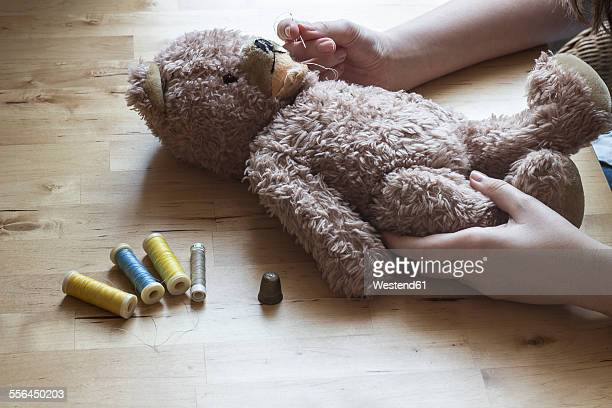 Womans hands repairing old teddy-bear