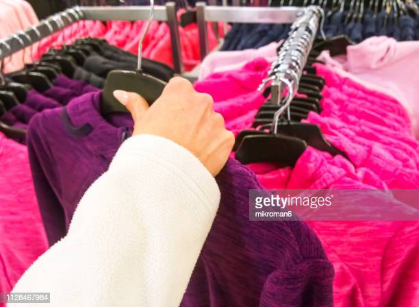 woman's hands selecting cloths in fashion store - purple dress stock pictures, royalty-free photos & images