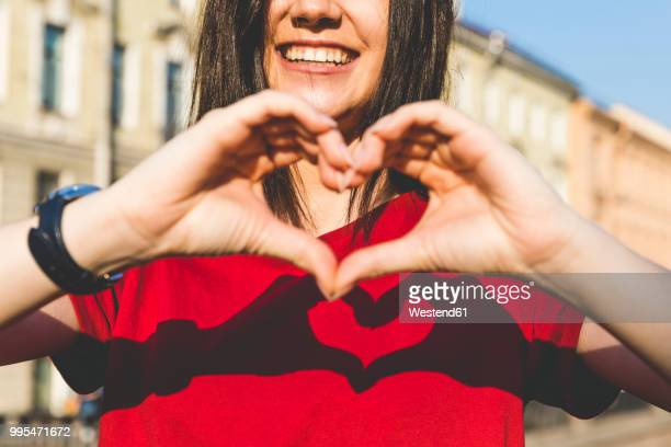 woman's hands shaping heart, shadow on red t-shirt - red shirt stock pictures, royalty-free photos & images