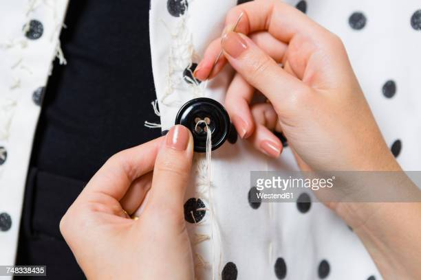 Womans hands stitching button on a dress, close-up