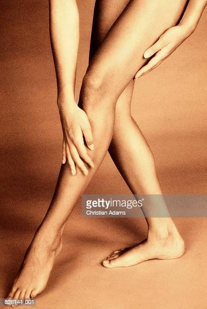 Woman's hands stretching down and touching naked legs (toned B&W)