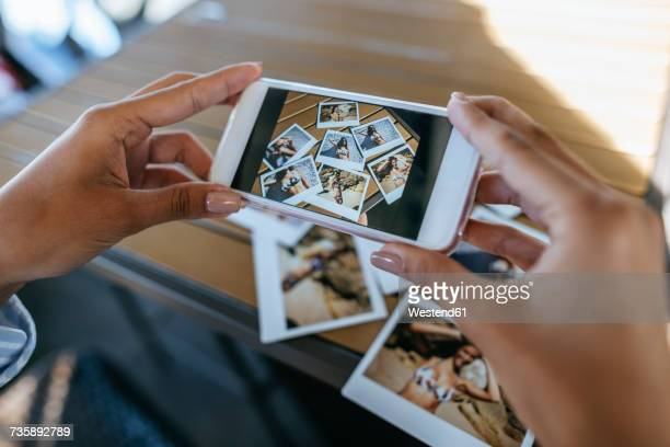 woman's hands taking picture of instant photos of herself with cell phone - photo messaging stock photos and pictures