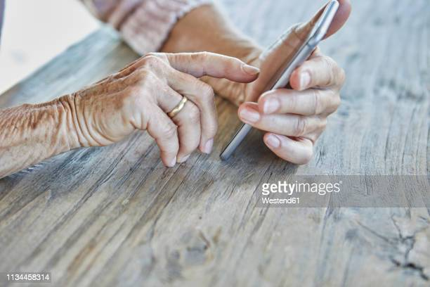 woman's hands using smartphone, close-up - seniorinnen stock-fotos und bilder