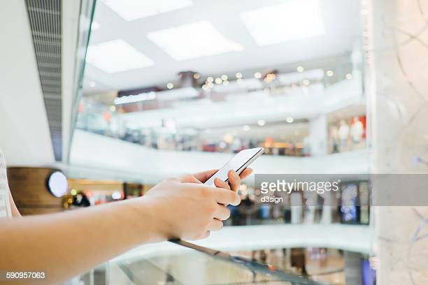 Woman's hands using smartphone in a shopping mall