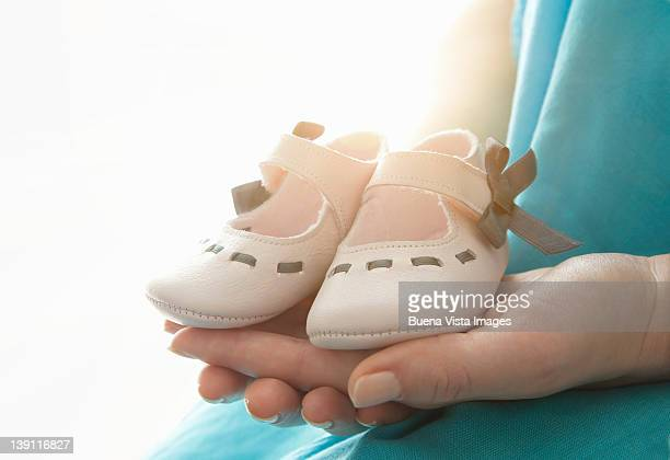Woman's hands with baby shoes