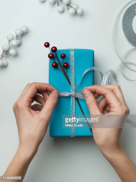 woman's hands wrapping holiday gift - donna bendata foto e immagini stock