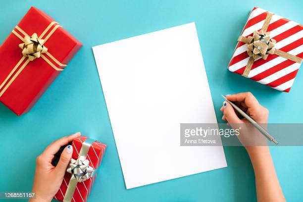 woman's hands writing to do list or list of new year resolutions - gifts stock pictures, royalty-free photos & images