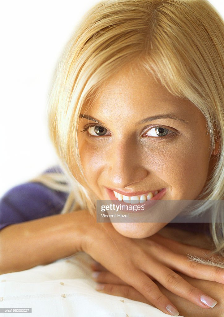 Woman's head resting on hands, smiling at camera, portrait, close-up : Stockfoto