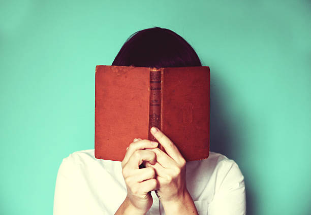 Woman`s holding a book in front of her face