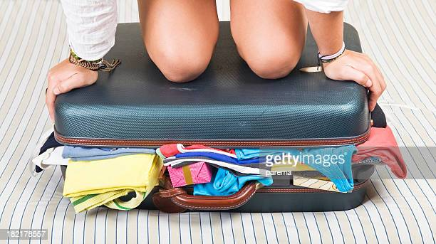Woman's knees and hands on a suitcase full of clothes
