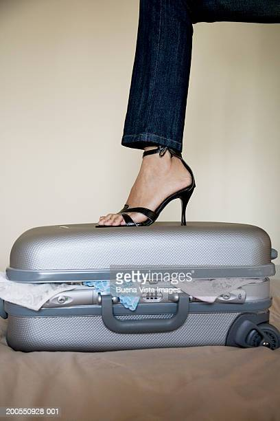 Woman's leg on suitcase, close-up